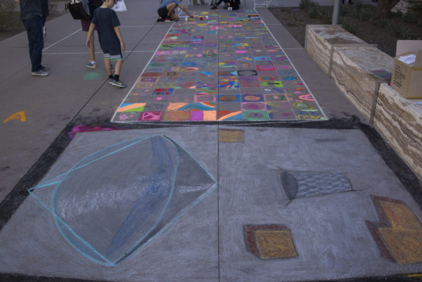 This photograph shows the full-size Psyche spacecraft outline drawn in sidewalk chalk. The bus (body) was completed by the artist, Brianna, but individual squares on the solar panels were filled in by children and visitors with any space image they chose.