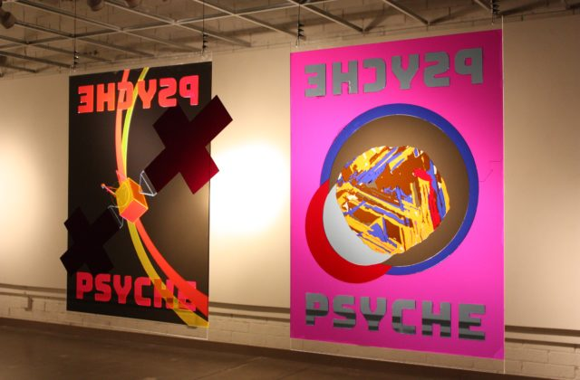 Two posters made from brightly-colored transparent acrylic cut and fit together; one shows the Psyche spacecraft, the other the asteroid. A colorful image is cast behind each poster when lit from one side.
