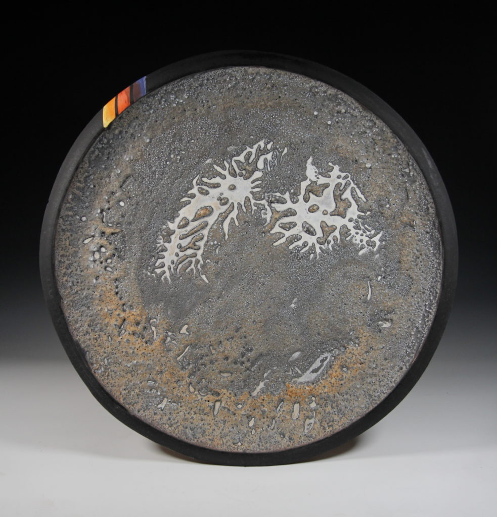 This image shows a circular ceramic platter. The center is grey with swirls and bubbles. The rim is black with three lines in colors of yellows, oranges, and purples.