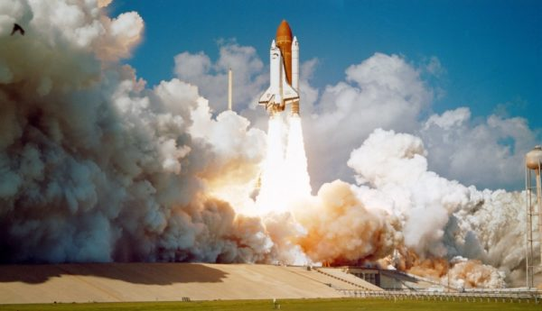 This image shows the Space Shuttle lifting off with large plumes beneath it.