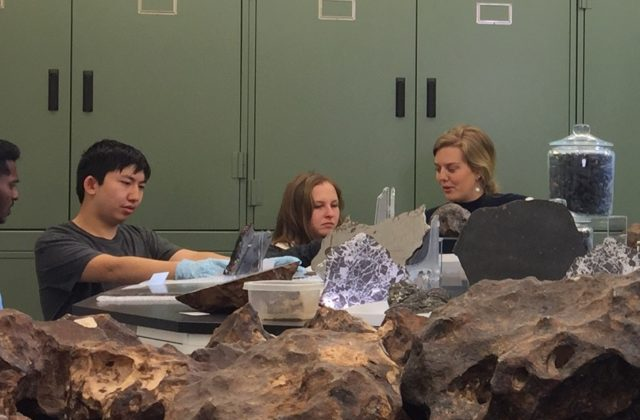 This image shows four university students who are participating in Psyche capstones discussing their projects inside the meteorite vault at Arizona State University's Center for Meteorite Studies.