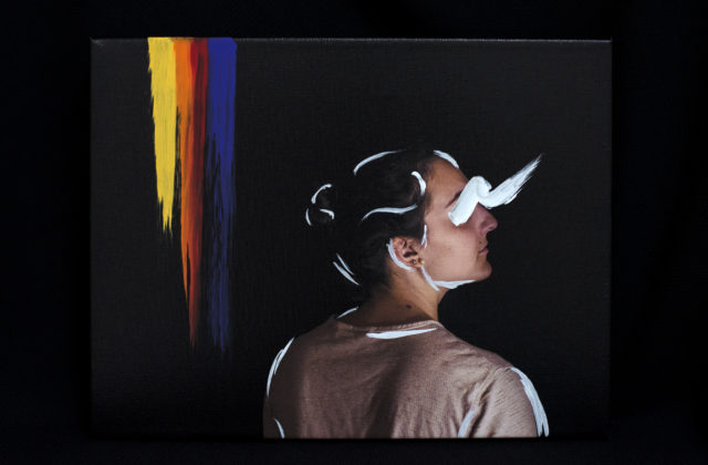 This is a photograph of a woman looking outwards and upwards. The background is gray and black and there are painted stripes of yellow, orange, red, and purple along one side. The woman's outline is accentuated and her eyes are obscured with white paint.