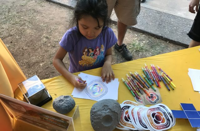 This image shows a young child intently coloring in the Psyche badge.
