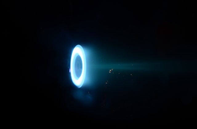This image shows the Hall thruster, a donut-shaped ring glowing blue on a black background.