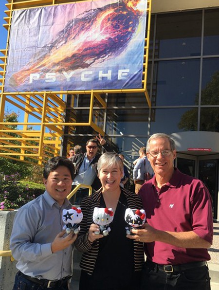 This photograph shows David Oh, Lindy Elkins-Tanton, and Dan Goebel holding small stuffed animals in front of a Psyche banner.