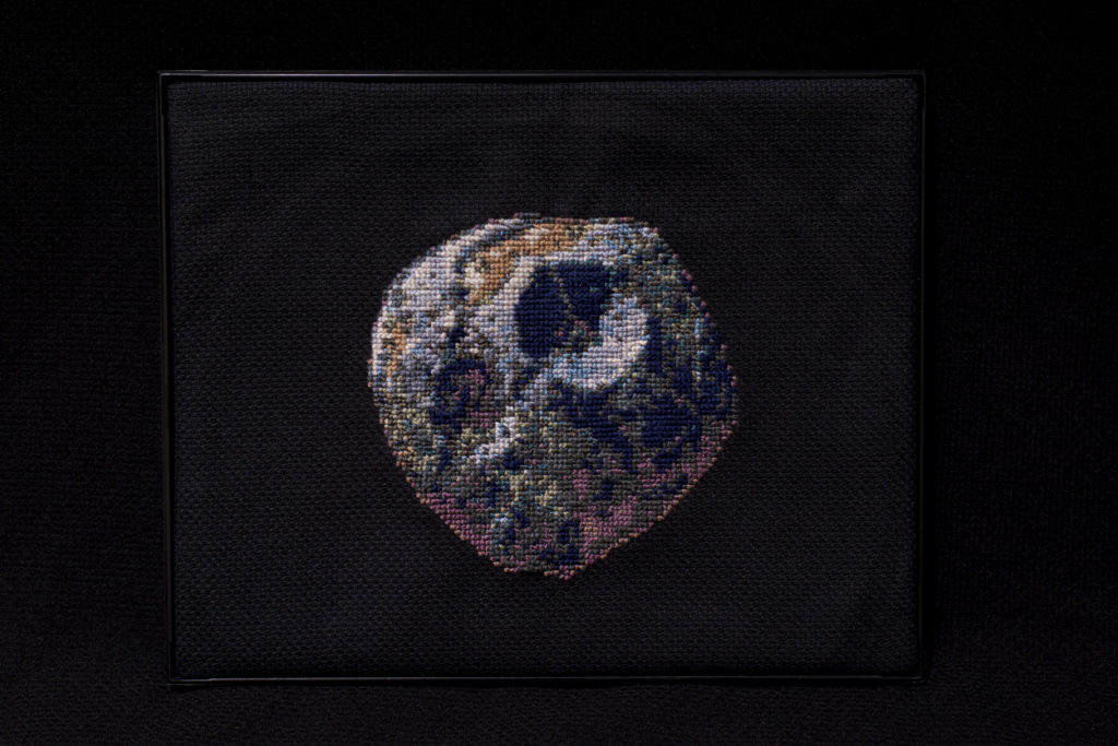 This image shows a cross stitch version of the artist's rendition of the Psyche asteroid on a black background. It shows the possible cratering and detail of the surface.