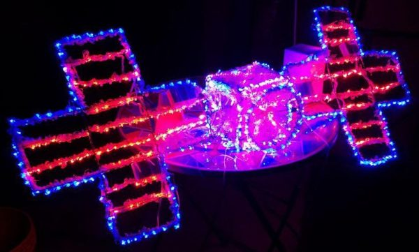 This image shows a sculpture made out of wire and LED holiday lights (pinks, reds, and blues) in the shape of the Psyche spacecraft.