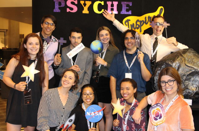 This picture shows 10 psyche inspired interns in the psyche photo booth holding psyche props.