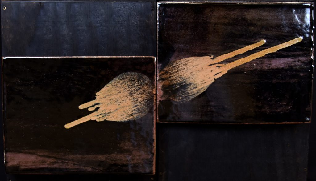 This image shows two large, offset ceramic slabs with dark, mostly-black backgrounds and orange-beige planet-like round objects hurtling toward collision at the center.