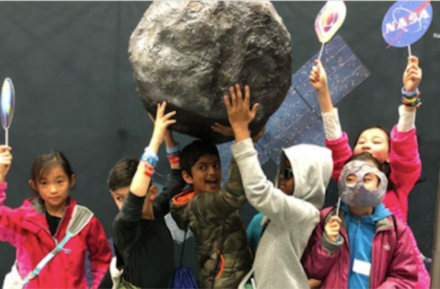 Little kids hold up the fake psyche asteroid along with psyche props.