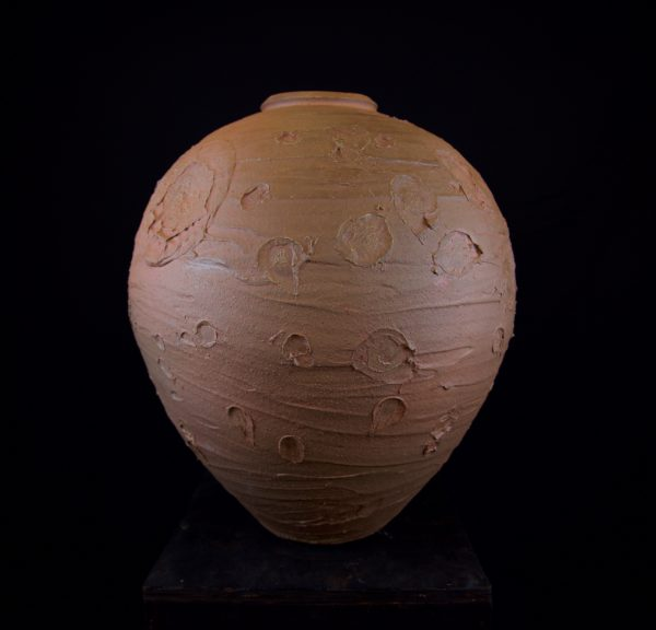 This image shows a large ceramic vessel, reddish in color and covered in rough craters and streaks.