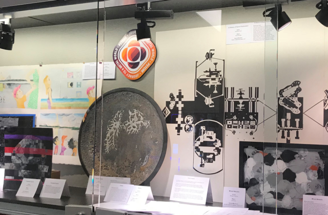 This image shows a glass case housing a range of Psyche Inspired artworks from the 2017-2018 year (Titanium Class)