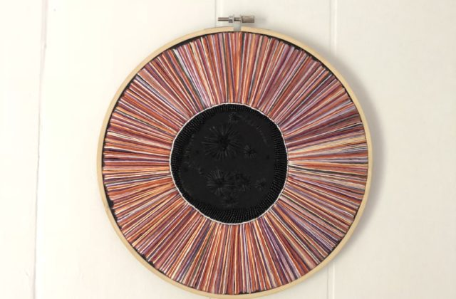 "A 9"" wooden hoop with Psyche's silhouette outlined in black beading, surrounded by rays of purple and orange stretching outward to fill the hoop."