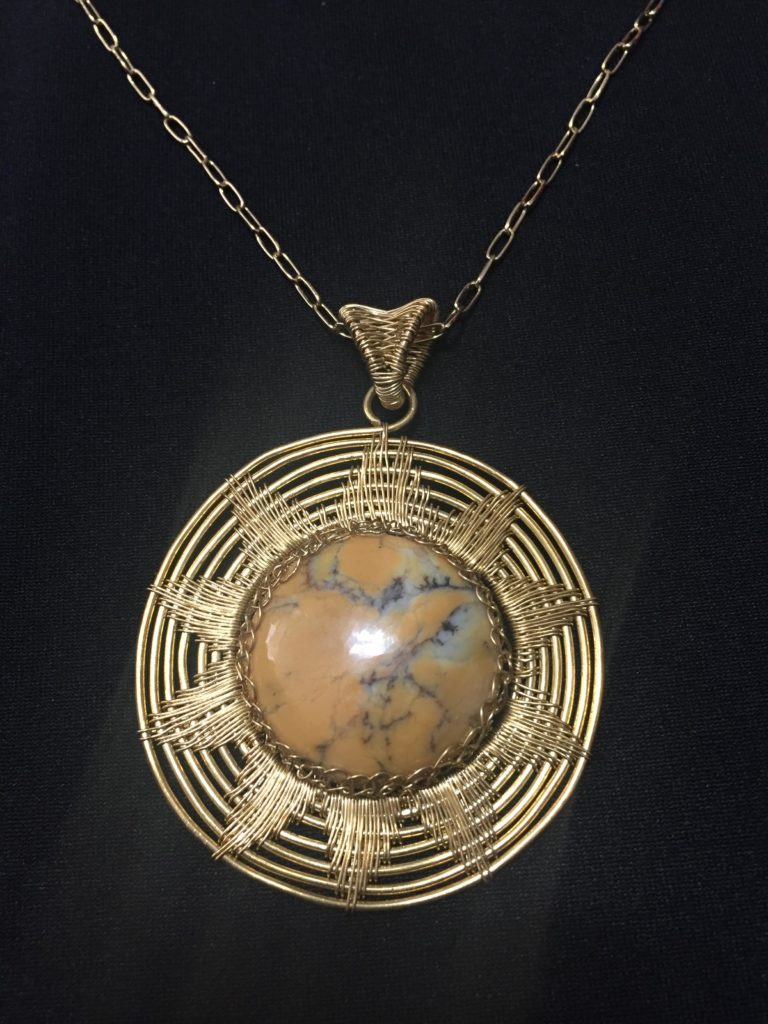 Circular pendant made from orange dendritic opal wrapped with brass wire, in a pattern shaped like the sun.