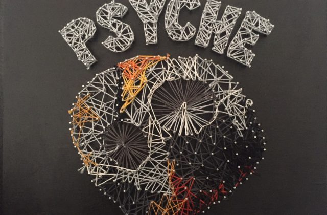 This piece features Psyche against a black wooden background. The shape of Psyche is composed of many tiny nails, with string wrapped around them. In this jumbled string, the two biggest craters stand out. They keep their signature circular shape. The asteroid has tints of orange and yellow at the bottom of it and on top, signifying metal. On top of the asteroid, also in string and nails, is the word PSYCHE in all caps and grey.