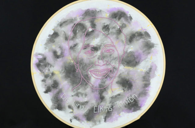 An embroidered portrait of Dr. Lindy Elkins-Tanton is centered on a watercolored image of Psyche.