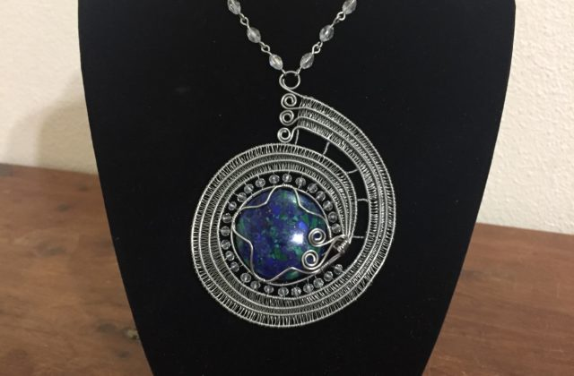 a necklace that has a blue central stone to represent the Earth and three thick silver wires wrapping around the stone similar to the Psyche spacecraft's flight path.