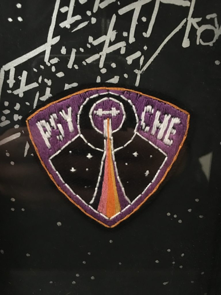 An embroidered rounded triangle, purple with a golden outline. Inside is a rainbow trail leading upwards towards a small image of the orbiter, two crosses with a square in the middle. The orbiter is surrounded by two circles. On either side of the circles are P S Y and C H E in white.