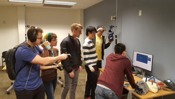This image shows six undergraduates clustered around a computer testing an Oculus Rift experience of the Psyche spacecraft.