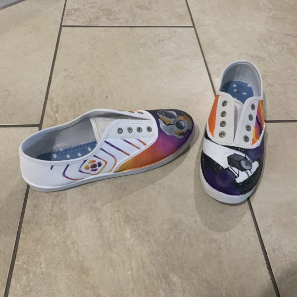 On the left shoe, at the toe area, there is a semi realistic painting of the Psyche asteroid. The background is a gradient from yellow to purple. On the outside of the left shoe is the logo for Psyche Inspired. The diamond shaped lines that have a similar gradient is extended to cover the whole outside of the shoe. The inside side of the left shoe is a vibrant orange. On the right shoe, at the toe area, is the spacecraft. It is slightly tilted, cutting off by the edges. The background is black and starry. The outside side of the right shoe is meant to be a