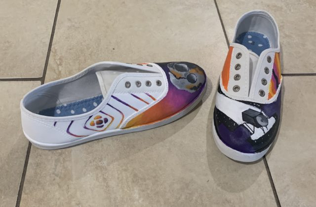 "On the left shoe, at the toe area, there is a semi realistic painting of the Psyche asteroid. The background is a gradient from yellow to purple. On the outside of the left shoe is the logo for Psyche Inspired. The diamond shaped lines that have a similar gradient is extended to cover the whole outside of the shoe. The inside side of the left shoe is a vibrant orange. On the right shoe, at the toe area, is the spacecraft. It is slightly tilted, cutting off by the edges. The background is black and starry. The outside side of the right shoe is meant to be a ""groovy"" pattern. There are wavy stripes alternating between the signature yellow, orange, pink, and purple found in the logo. The inside side of the right shoe is also a vibrant orange. Keeping both insides a vibrant orange brings the shoe together and makes them seem more like a pair of shoes rather than two completely different shoes with different designs."