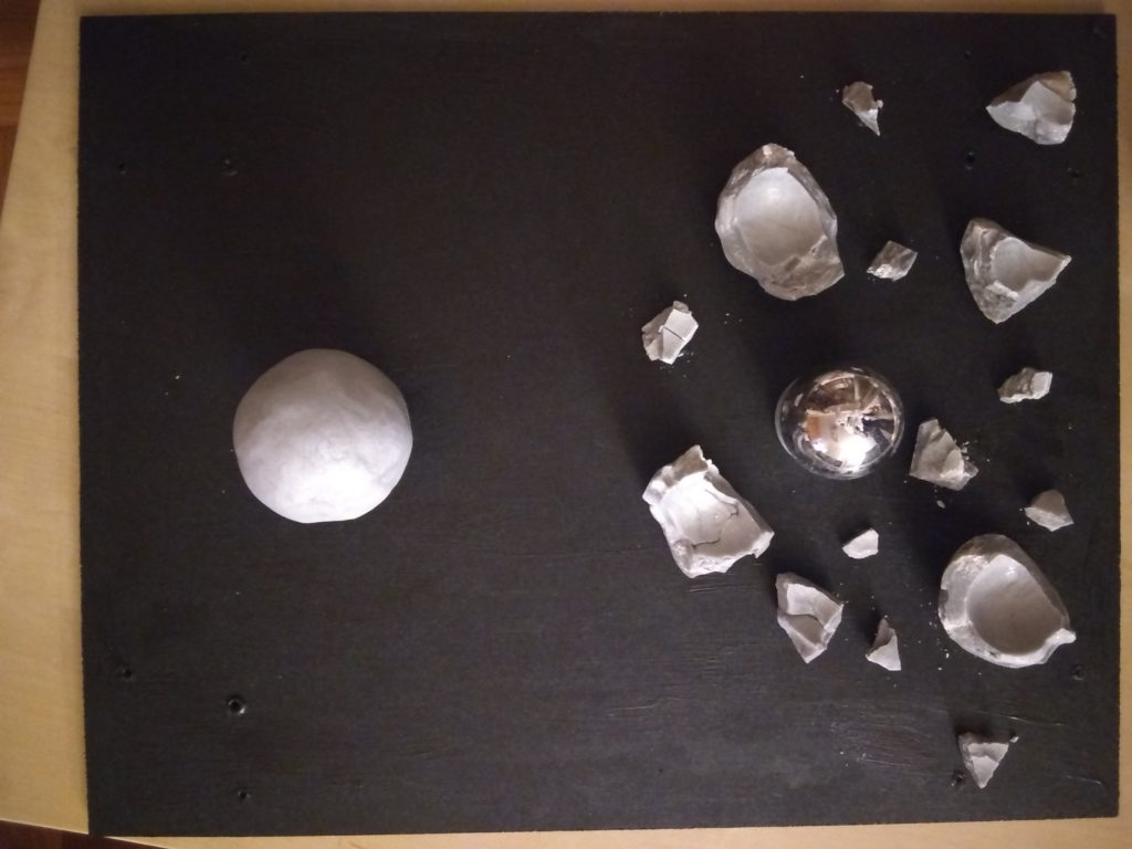 The video shows a gray ball being smashed into fragments by a rock, revealing a silver ball inside. The photo shows the fragments and silver ball arranged on a black board, with another gray ball nearby.