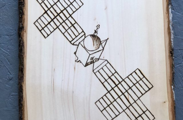 This image shows a vertical slice of wood with an image of the Psyche spacecraft made using woodburning.