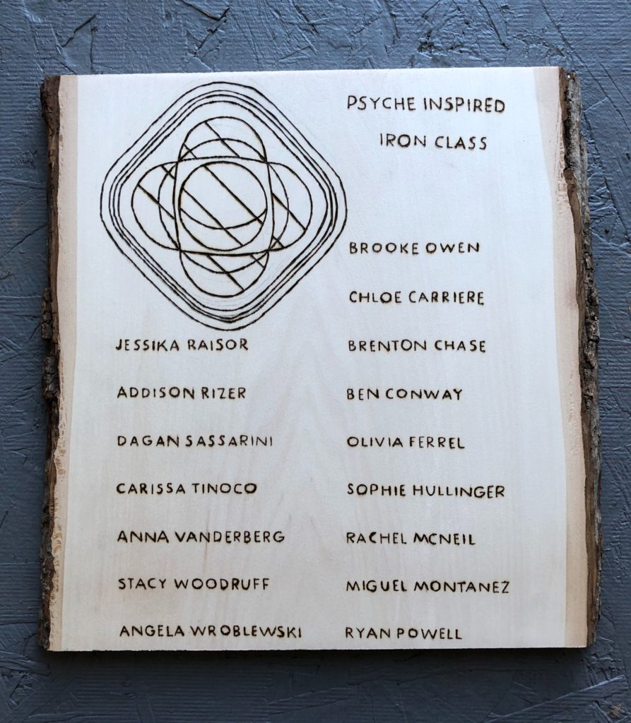This image shows a vertical slice of wood with the names of the Psyche Inspired interns listed using woodburning.