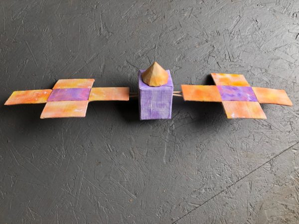 A handmade purple and orange psyche spacecraft constructed of cardboard, papier-mâché, flour sack towels, and watercolor.