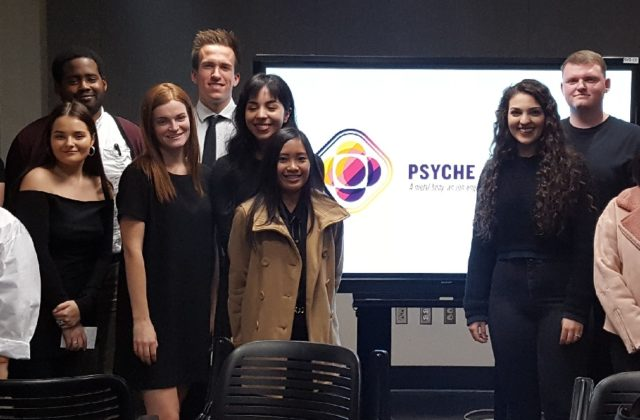 This image shows students and faculty from the graphic design capstone at ASU. They are standing in front of a screen showing the Psyche name and logo.