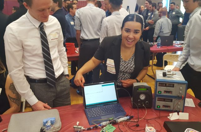 Undergraduate students displaying their protoype controlled by a laptop.