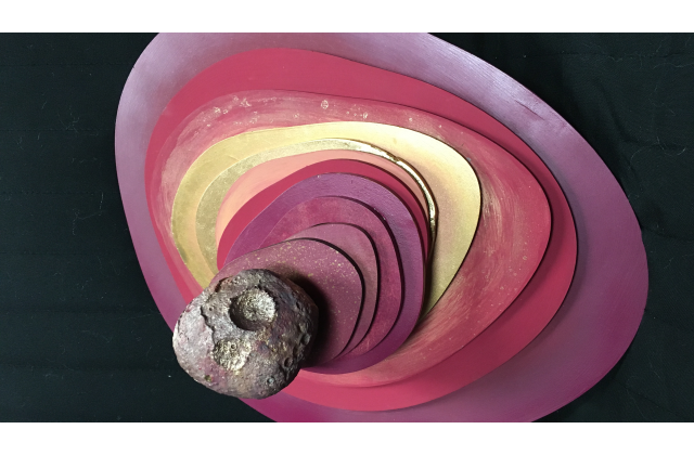 Foot-by-foot concentric organic shapes are stacked and spiraling towards the viewer in pinks, oranges and golds leading towards the gray, 3D printed Psyche Asteroid. Dry brushed pinks and gold follow the contour lines of the 3D print.