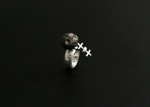 This image shows a sterling silver kinetic ring with a darkened bronze asteroid as the centerpiece. A tiny spacecraft placed next to the asteroid is mobile. The small spacecraft can be pushed around the asteroid to simulate orbit.