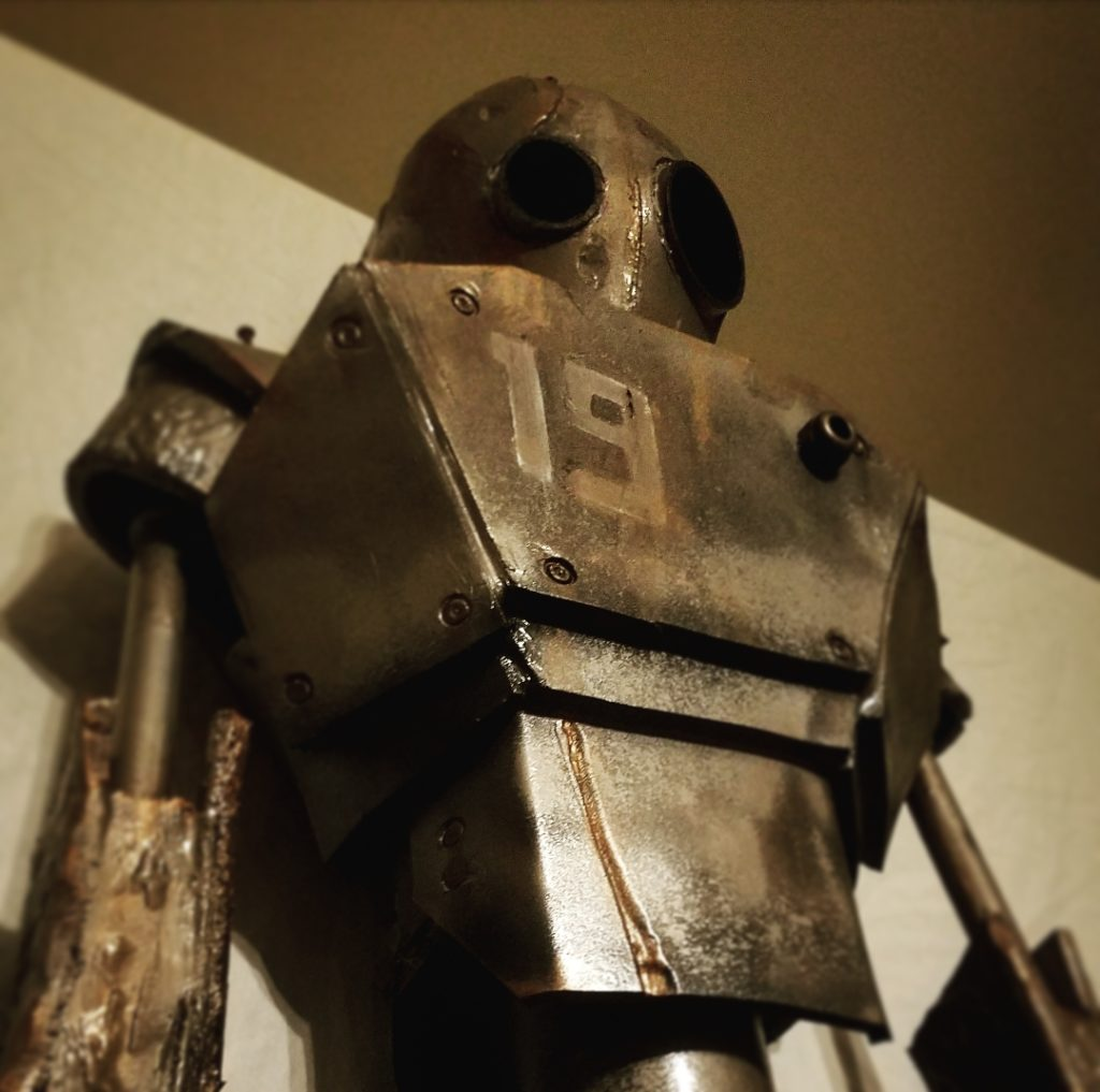 A robot stands 6ft tall with the number 19 displayed on its chest. There is rust coming from the edges of the plating. There are dents and scratches covering the robot's head, arms, and chest. It seems to be looking at something in the distance with dark, black lenses–one of them larger than the other. The background is white, bringing a dynamic contrast to the dark bronze metallic glow of the robot's plating.