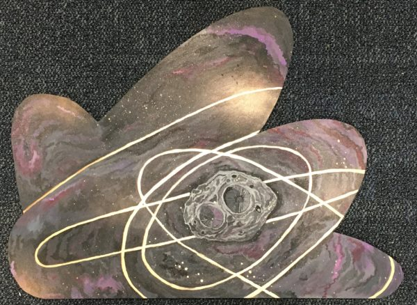 This piece shows trajectory lines framing Psyche. The project highlights the asteroid and shows the Psyche orbiter dancing with the space object. Black, purple and pink clouds were painted with rosy golds to create visual interest. Psyche is painted in the middle towards the right with rings of gold around it, signifying paths the Psyche orbiter might take. Spray paint gold was used to make speckled stars and clouds of gold in the background.