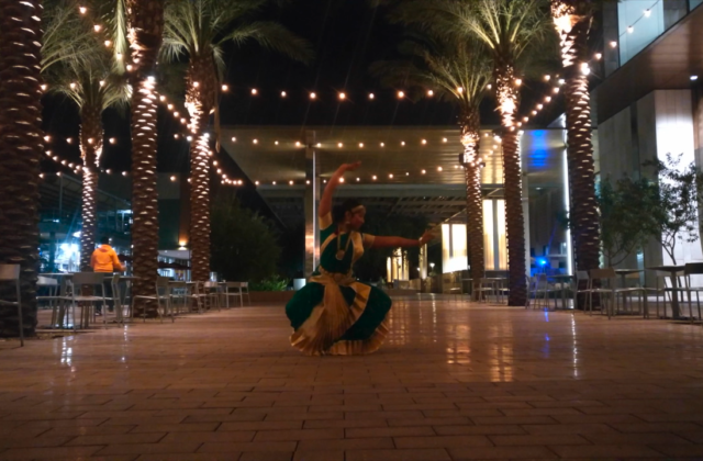 The dancer is wearing a teal and white silk traditional costume with a distinctive sweeping fan between the legs of the costume bottom to highlight the dancer's sitting posture. The video alternates between shots of the dancer reciting the jathi with rhythm kept on her fingers, and the dancer performing the dance outdoors flanked by palm trees hung with fairy lights.
