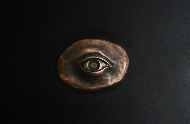 An oval-shaped art piece cast in bronze in the shape of an eye with a glass pupil. The pupil is a magnification lens through which one can view an image of Psyche in human form looking up at a spacecraft traveling toward her.
