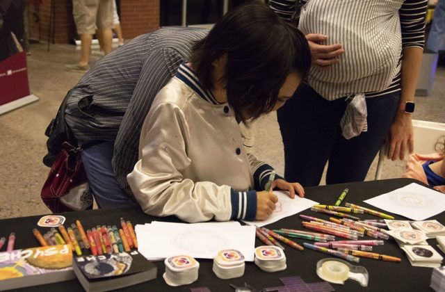 Child coloring a Psyche mission badge picture at a public event.