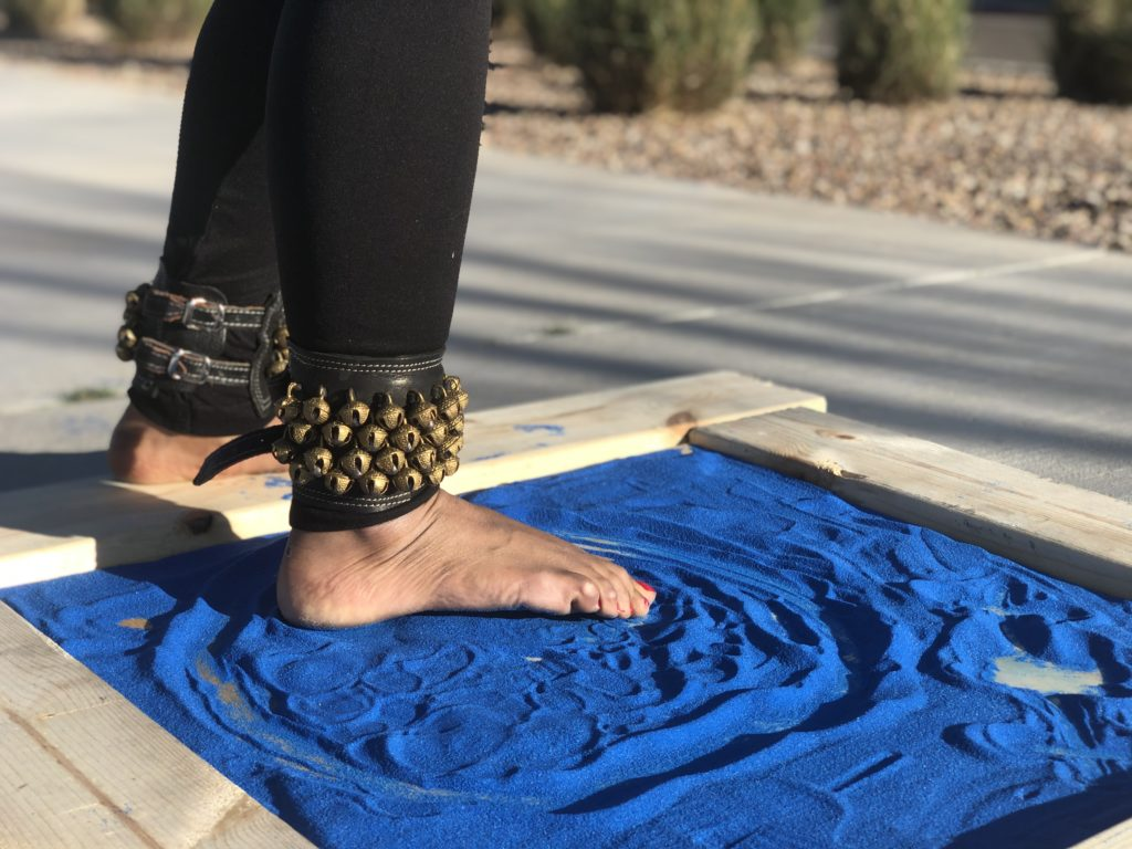 A dancer's feet are posed and tracing an image in bright blue sand poured into a framed flat surface. The traced image is a simplistic representation of the Psyche spacecraft orbiting the asteroid (16) Psyche