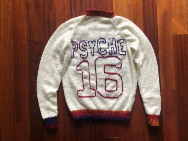 """On the front, left side of a white sweater, there's a purple outline of the Psyche spacecraft with a small pink signal wave. On the back of the sweater is a large number 16 with the word """"PSYCHE"""" spelled in all caps, placed like the design of a sports jersey. The collar, sleeve cuffs, lower band, letters, and numbers of the sweater are in an ombre yarn of purple, pink, red, and orange."""
