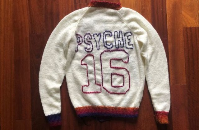 "On the front, left side of a white sweater, there's a purple outline of the Psyche spacecraft with a small pink signal wave. On the back of the sweater is a large number 16 with the word ""PSYCHE"" spelled in all caps, placed like the design of a sports jersey. The collar, sleeve cuffs, lower band, letters, and numbers of the sweater are in an ombre yarn of purple, pink, red, and orange."