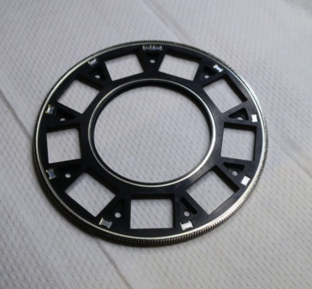 """This image shows a black circular wheel with rectangular holes cut out and many tiny """"teeth"""" along the outer rim."""