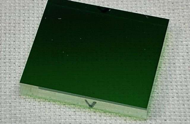 Small green glass rectangle on white woven material.