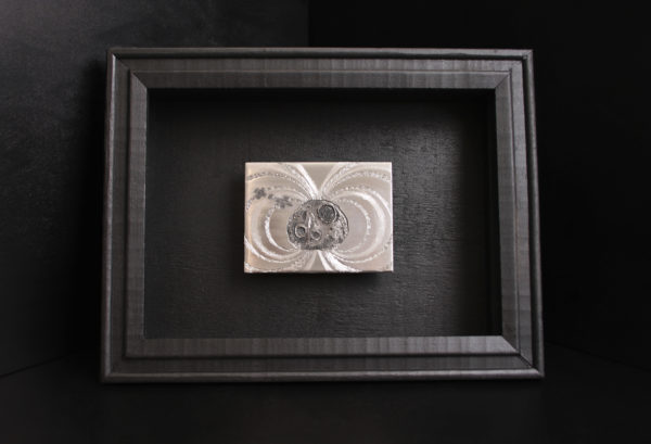 Here, a hand engraved steel plate depics an image of the Psyche asteroid with the Psyche spacecraft and radiating magnetic field. The plate is mounted on a black shadowbox frame.