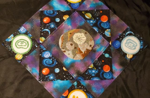Beaded Orbits is a 2' x 2' quilt with four beaded medallions representing the phases of orbits placed in each corner and a beaded Psyche in the center. They are attached to fabric of celestial and space themed designs. The quilt layout of the fabric represents the dreams space exploration inspire, and I chose to laboriously bead as a nod to how much work goes into a mission.