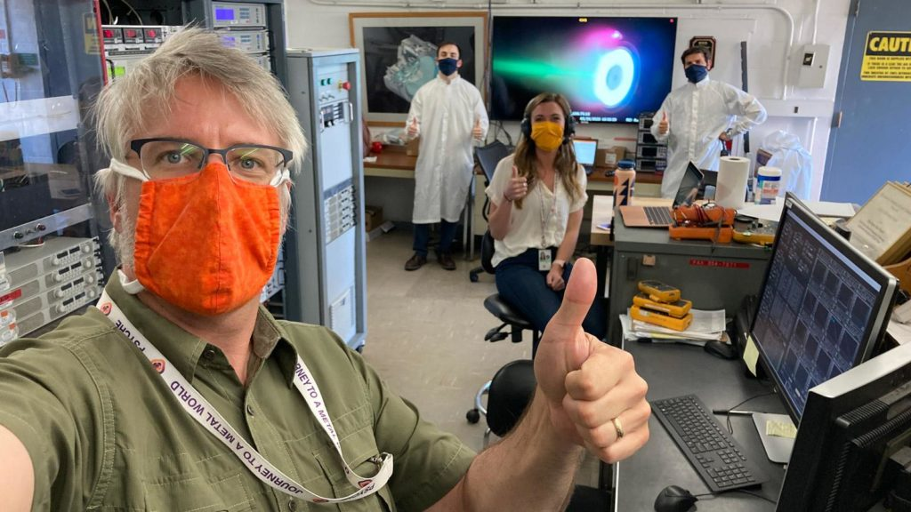 Scientist in a lab wearing masks while holding their thumbs up.