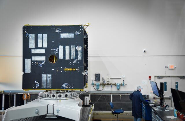 The body of the Psyche spacecraft is in progress. This image shows a black box with many wires sticking out of it and an engineer standing nearby.