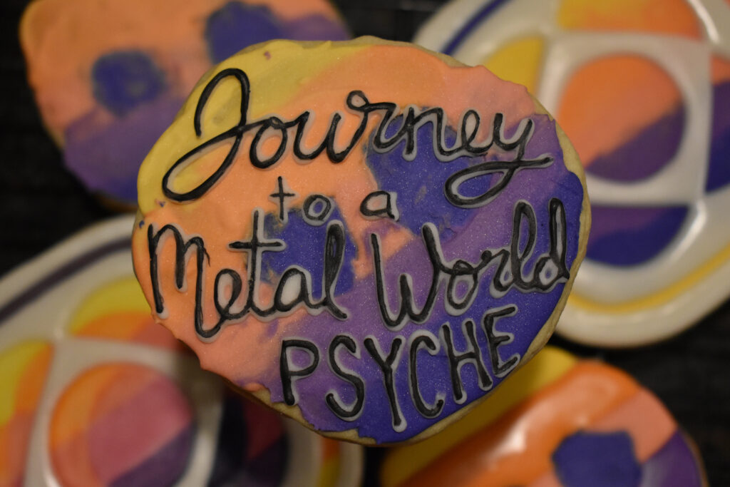 "An asteroid-shaped cookie of the Psyche mission badge with black lettering that says, ""Journey to a Metal World PSYCHE,"" is centered in the foreground. Mission badge and asteroid cookies of the same yellow, orange, pink, and purple gradient are in the background."