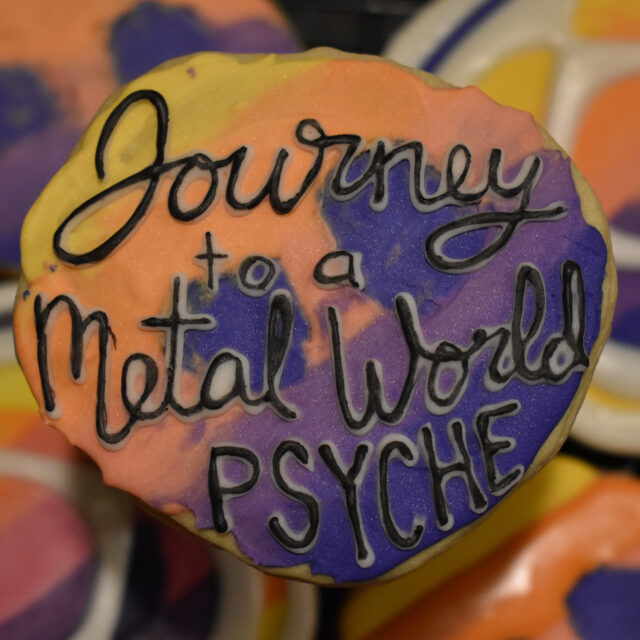 """An asteroid-shaped cookie of the Psyche mission badge with black lettering that says, """"Journey to a Metal World PSYCHE,"""" is centered in the foreground. Mission badge and asteroid cookies of the same yellow, orange, pink, and purple gradient are in the background."""