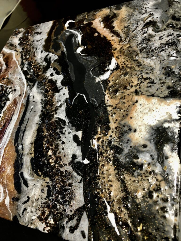This abstract piece has gold, orange, and red streaks of paint on the bottom left corner with black crystals sprinkled over it. The paint is blended with black and white streaks. The black crystal textures and gold and silver glitter are present in most of the piece. The overall piece has a marble-like finish and appearance.